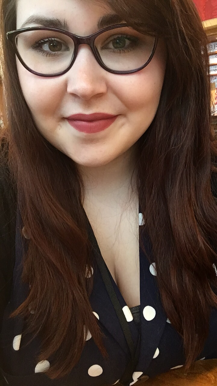 A selfie style image of Holly a 21 year old with long brown hair and purple slightly rounded glasses on. Holly is smiling at the camera and is wearing a nude/pink/brown lipstick. Holly is also wearing a dark blue shirt with medium white spots on it. There is also a black lanyard around her neck.