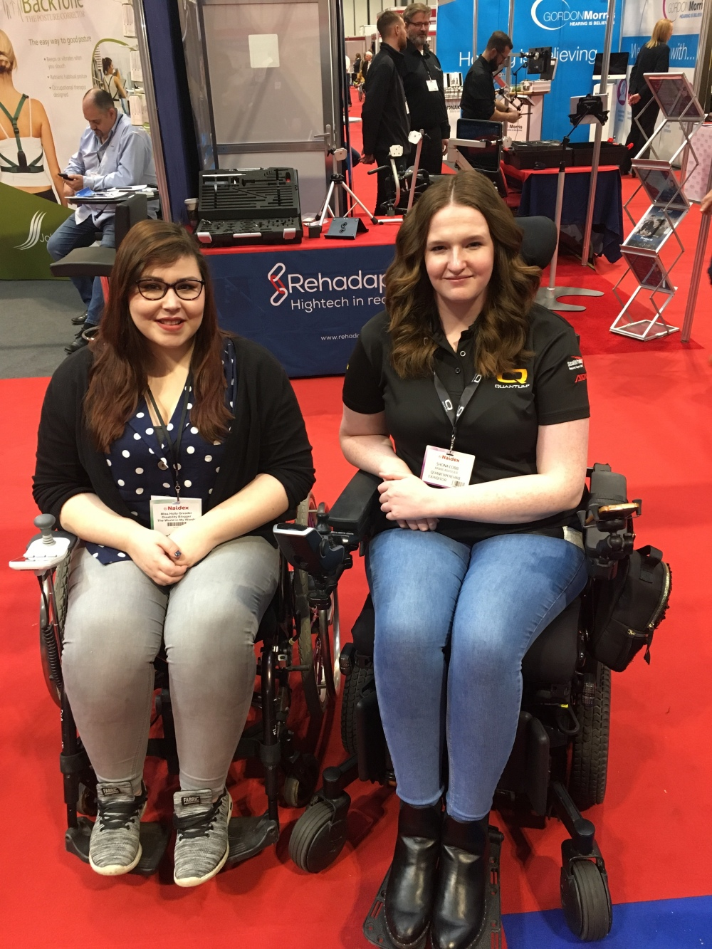 A imagine of two women in their wheelchairs on red carpet with stands behind them. On the left Holly sit in her wheelchair with her hands on her lap. Wearing a blue shirt with white Polka dots and a black Cardigan. A black lanyard is hanging around her neck with her name on it. On the right is Shona she is sitting in her wheelchair with her hands to the side. She is wearing light blue jeans and a black polo neck top. She also has a black lanyard around her neck with her name on