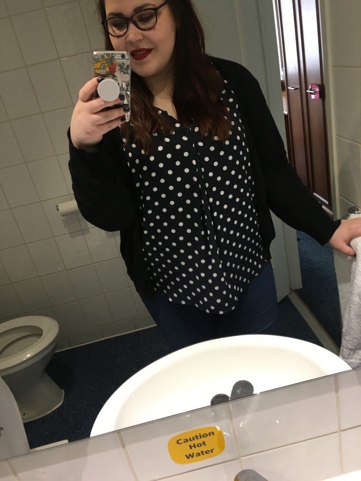 Holly is taking a selfie in a bathroom mirror. You can see part of a white sink and a toilet. Holly is holding onto a towel and towel rail on the right. She is wearing dark blue jeans with a dark blue blouse with white Polka dots and a black Cardigan. Her hair is long and brown she is also wearing red lipstick and purple rounded glasses. Her phone is also in her hand taking the picture.