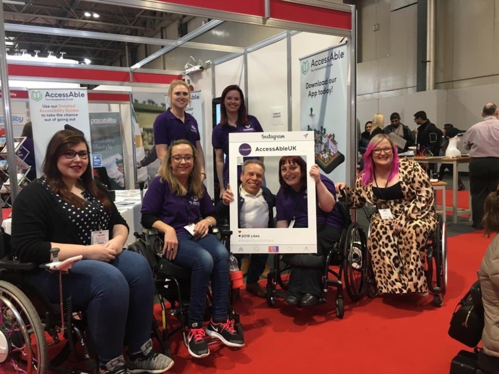 A group photo in front of the AccessAble stand. On the left are Holly and Carrie-Ann sat in their wheelchairs, in the middle is Warwick Daivs and Lucy in her wheelchair together holding an AccessAble Instagram cut out board. Behind them stands two of the AccessAble team. On the right sits Emily Yates. Everyone is smiling at the camera.