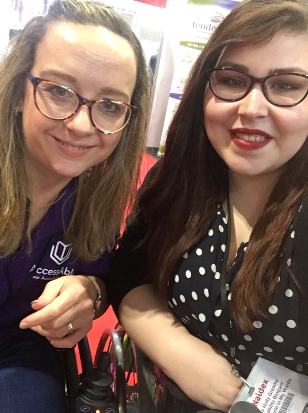 A picture of two women. On the left is Carrie-Ann who has blonde/brown hair with slightly rounded glasses on and a purple t-shirt. Carrie-Ann is leaning on the arm rest of her wheelchair she is sat in. On the right is Holly with long brown hair, purple slightly rounded glasses and red lipstick. Holly is wearing a dark blue blouse with white Polka dots on. She is also leaning on the arm of the wheelchair she is sat in.