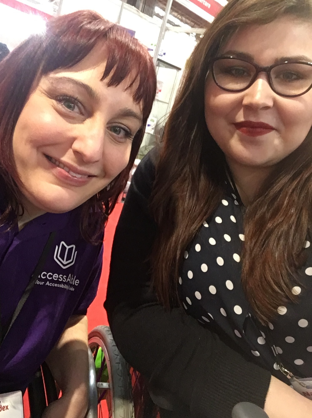 Two women sitting next to each other both leaning on the arms of their wheelchairs. On the left is Lucy with brown/red hair she is smiling at the camera and wearing a purple polo shirt which says AccessAble on it. On the right sits Holly she has long brown hair, slightly rounded purple glasses, she is wearing red lipstick. She is wearing a dark blue blouse with white polka dots and a black cardigan.