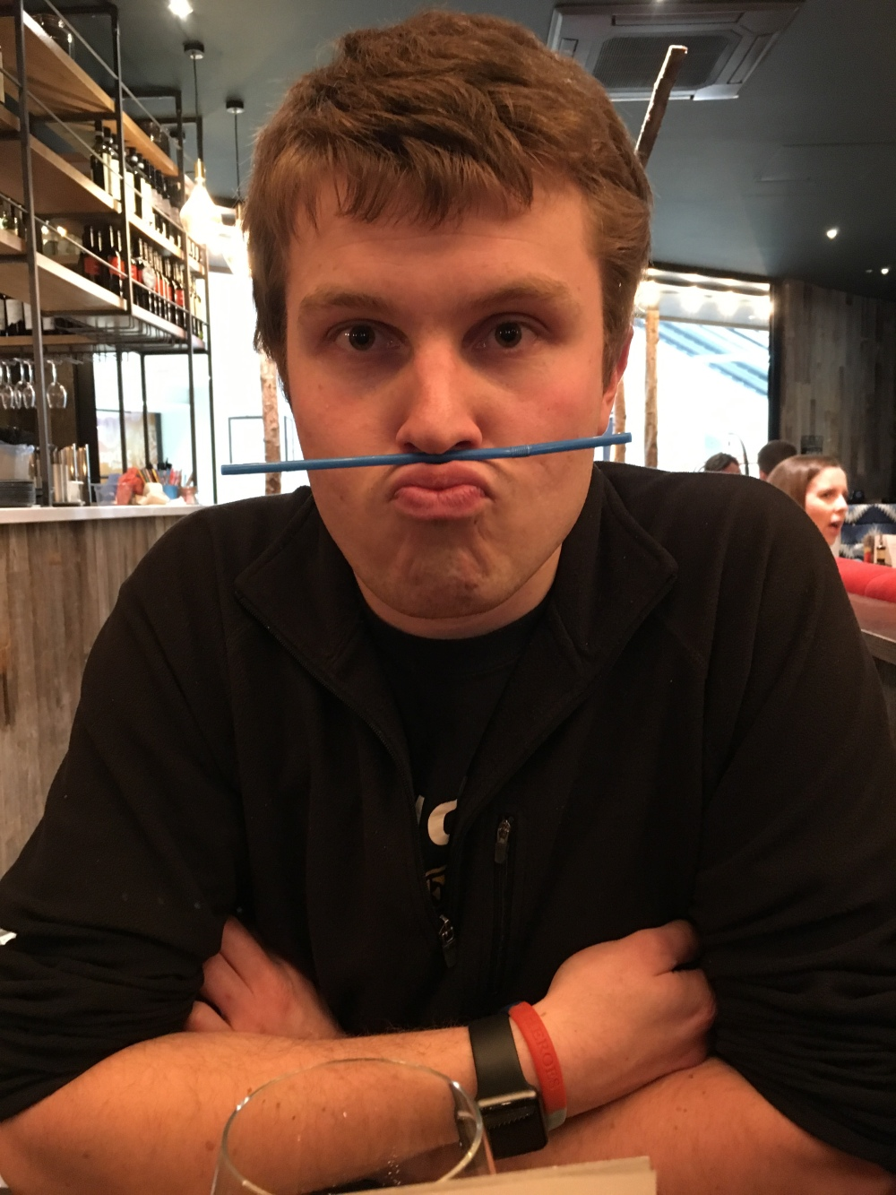 A photo of James a 23 year old with slightly wavy short brown hair. He has his arms crossed and is wearing a black jumper. He is pursing his lips pushing them out and up to hold a straw between his lips and nose. In the background you see other restaurant customers and part of the bar.