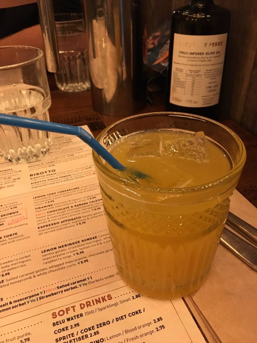 A short decorative glass with a yellow/orange liquid and ice in as well as a blue plastic bendy straw. The glass is sat on a menu and white napkin. There are other general restaurant item in the background including a water glass, olive oil and water jug.