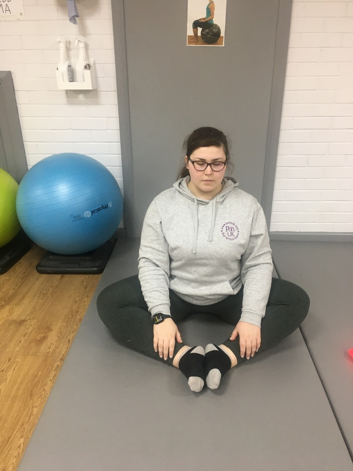 Holly is sitting in a gym. She is sat on a grey gym mat with a a blue and green gym ball sat beside her. She is sat in an upright posture.