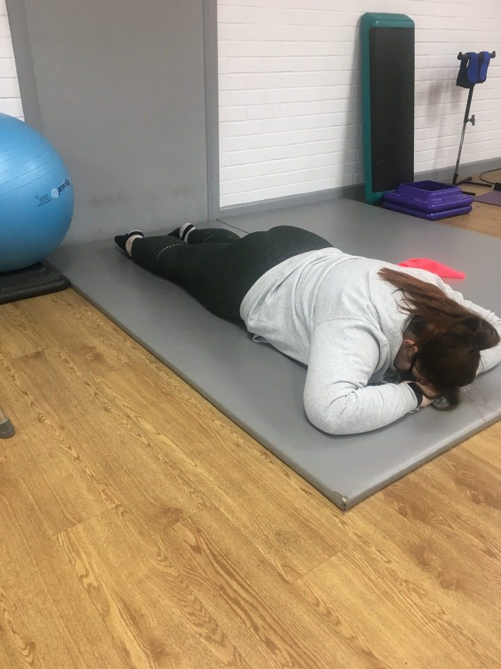 Holly is sitting in a gym. She is lying on a grey gym mat with a a blue and green gym ball sat beside her. She is lying on her front stretching out her legs.