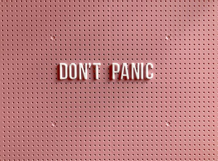 A small pink peg board with white letters in the centre reading 'don't panic'.
