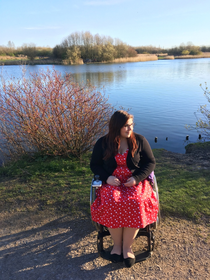 Holly is sitting in front of a blue lake with trees around. She is sat in her wheelchair wearing a red polka dot dress